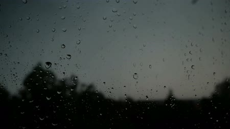 nemli : Storm with a thunderstorm outside the window. Rain drops on the glass. Lightning discharge.