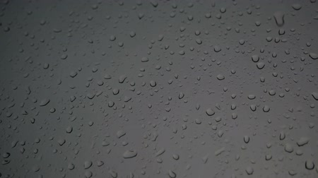 Drops of rain fall on the window glass and flow along it.