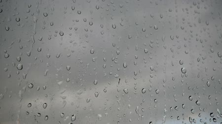 Large number of drops from the rain on the window glass. Stream of water swiftly flow down the glass.