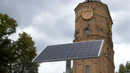 Small solar battery installed in the park near the clock tower. Analog technologies and nanotechnologies in everyday life. Transformation of solar energy. The old building on the background. Стоковые видеозаписи