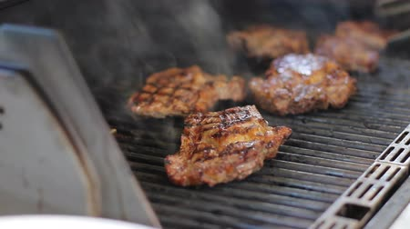 Meat steaks are cooked on a gas grill. Tasty meat dishes in the open air. Smoke comes from food. Cook turns the beef with metal tongs.