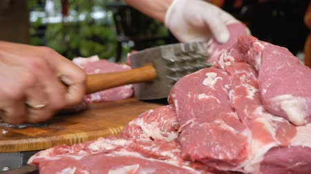 dana eti : The butcher beats pieces of pork with a large hammer. The cook prepares the meat before cooking. A large mountain of meat in the foreground.