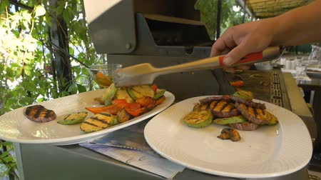 инструмент : Cook lay out on plates with help of forceps various vegetables such as eggplant, pepper, zucchini and mushrooms. Healthy food is cooked on the grill. Man is preparing to serve a deliciously cooked dish.