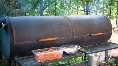 курильщик : Cooking of meat dishes outdoors. Large black outer grill from which smoke comes. Equipment for frying a large number of steaks and sausages.
