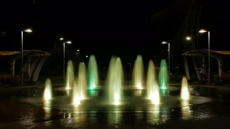 Timelapse video of a night glowing pedestrian fountain in the city. Water jets pounce high above the ground. Beautiful place for walking.