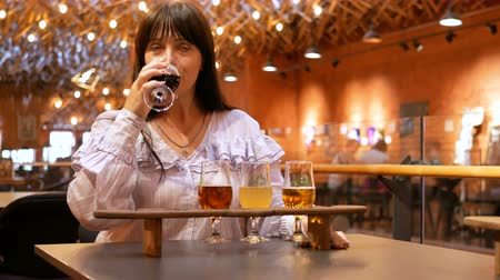 Adult woman tastes several types of beer in small glasses on a wooden stand. The taster did not like the drink very much. Preparation for the festival of beer. Stock mozgókép