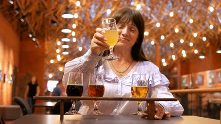 Adult woman drinks several kinds of beer in an interesting institution. The housekeeper spends her free time drinking low-alcohol drinks. Preparation for the festival of beer. Stock mozgókép