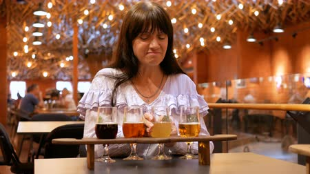 Adult woman tastes several types of beer in small glasses on a wooden stand. Taster did not like the drink very much. Not a single beer is suitable for a beautiful brunette.
