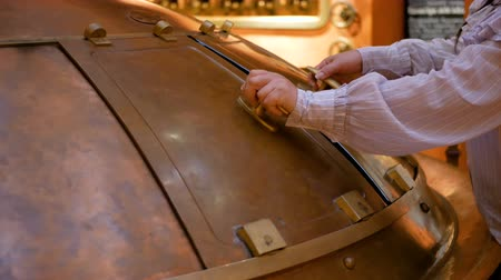 пивоваренный завод : The brewery worker opens the lid of the tank with beer malt from which the light is shining. Production of low-alcohol beverages.