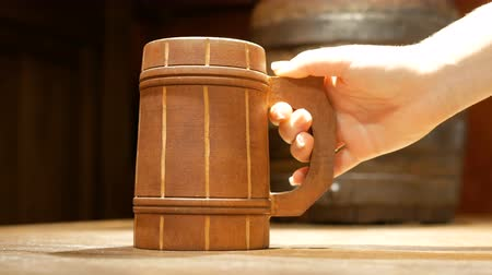 Human hand puts an old wooden beer mug on the table on the background of a small barrel for drinks. Dishes in the pub. Stock mozgókép