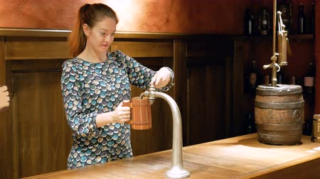 Октоберфест : Young woman pours beer from a tap into a wooden mug. Pretty brown-haired woman does her job and cute. The pub worker puts the drink on the table. The old barrel stands in the distance of the bar counter.