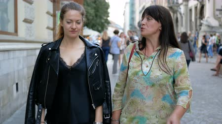 Adult daughter and a beautiful mother are walking along the city street and discuss something hotly. Beautifully dressed women on a walk.