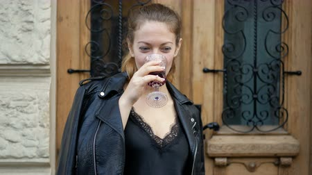 Young woman drinks wine from a crystal glass and enjoys a drink. Leisure of successful people on the road.