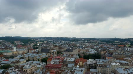 View from the altitude on the old city. Roofs of houses of different colors. The clouds flew over a cloudy city.