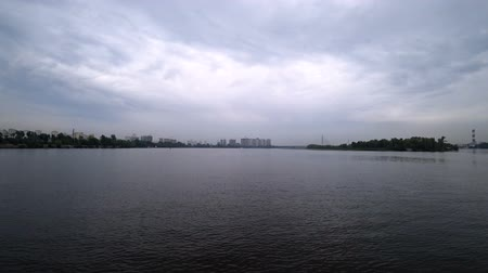 Time-lapse video on the river from a ship that sails to the coast of the city. Gloomy weather in the evening. Water transport sails by.