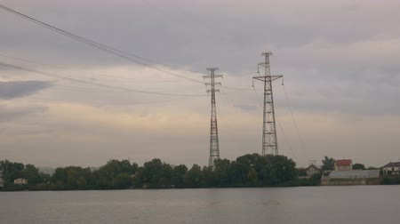 energetyka : High electrical piers on the river bank. Transmission of electricity over a distance.