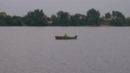 bilinmeyen : Fisherman on a small old boat in the middle of the river is fishing for a bait. Leisure and hobby of an unknown man. Shore and trees on the background.
