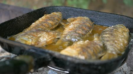 Cooking fish in oil in a frying pan and grill. Frying fish in the open air. Professional catering. Delicious crispy food. Junk food