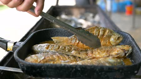 Cooking fish in oil in a frying pan and grill. Frying fish in the open air. Professional catering. Delicious crispy food. Cook by tongs turn over the dish