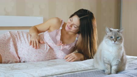 the fetus : A pregnant woman woke up and stroked her belly. The cat is sitting on the bed next to her. The girl smiles and looks at the pet.