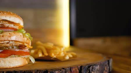 barbecue set : A large double burger with chicken is laying on a wooden board next to french fries. Professionally cooked fast food.