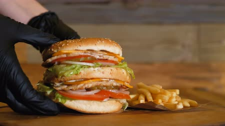 barbecue set : Black gloves put a juicy burger with two cutlets and vegetables on the wooden board next to the french fries. Unhealthy fast food. Stock Footage