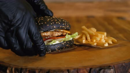 barbecue set : Hands in gloves pick up a juicy black burger with cutlets and vegetables. Unhealthy fast food. French fries remain on the wooden board.