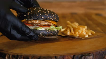 barbecue set : Hands in gloves put a juicy black burger with big cutlets and vegetables on the wooden board next to the french fries. Unhealthy fast food. Stock Footage
