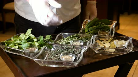 lényeg : Professional chef shows a gloved hand on various herbs for cooking in the ground and fresh. Healthy food in transparent glassware. Fragrant Spices