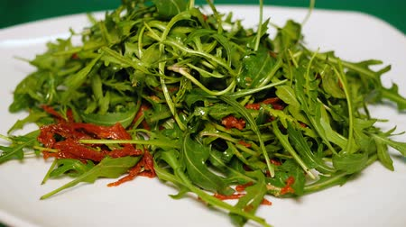 Salad of arugula and dried tomatoes rotate on a white plate. Healthy diet food close up. Unusual recipe dishes. Стоковые видеозаписи