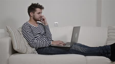 борода : Young man working on laptop sitting on the couch