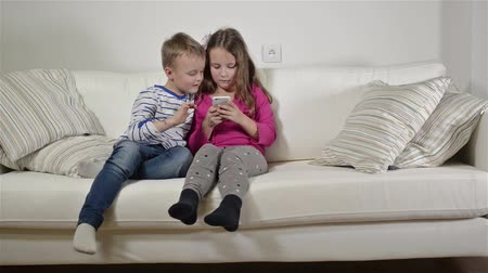 rodzeństwo : Children at home sitting on sofa, playing with smartphone