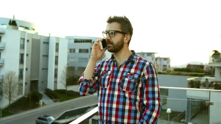 gündelik kıyafetler : Businessman with smartphone making phone call, standing on balco Stok Video