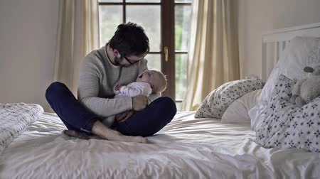 newborn child : Father holding his baby boy, sitting on a bed Stock Footage