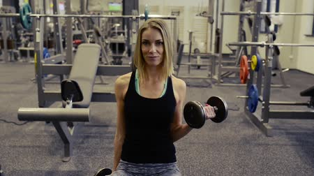 bicep : Beautiful blond woman in gym working out with weights