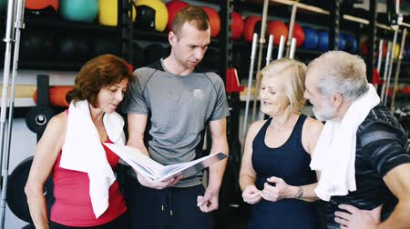 eğitici : Fit seniors in gym with personal trainer discussing fitness plan Stok Video