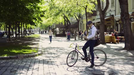 bisiklete binme : Mature businessman with smartphone and bicycle in the city.