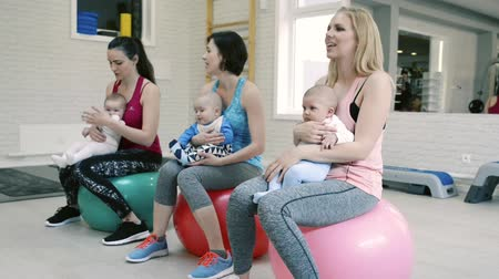 holding : Mothers exercising with babies in gym on gymnastic balls. Stock Footage