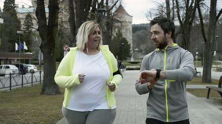 nadváha : Fitness trainer in town park running with overweight woman. Dostupné videozáznamy