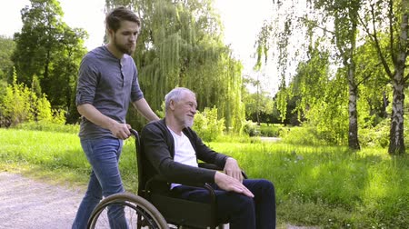 caregiver : Hipster son walking with disabled father in wheelchair at park.