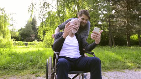 rokkant : Hipster son and father in wheelchair at park taking selfie.