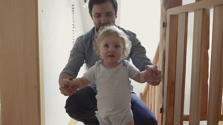 segítség : Young father at home with his little son doing first steps.
