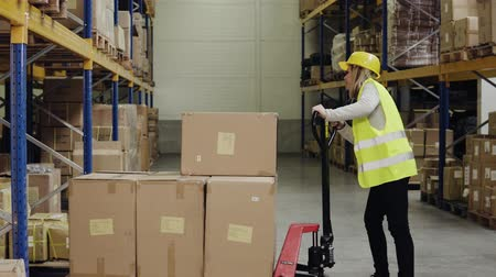 tektura : Female warehouse worker with hand forklift truck.