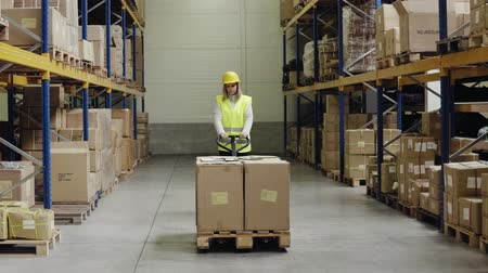 Female warehouse worker with hand forklift truck.