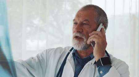 рентгенологическое : Senior doctor with smartphone looking at x-ray in office.