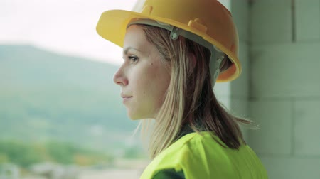 montáž : Young woman worker on the construction site.