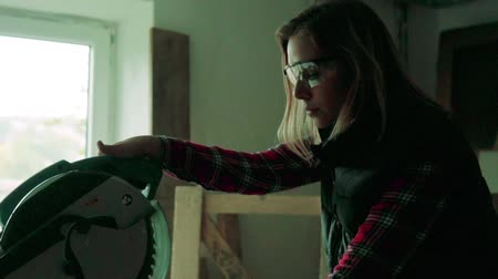 miter saw : Young woman worker in the carpenter workroom.