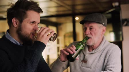 két : Senior father and his young son drinking beer in a pub.