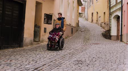 grandad : Senior father in wheelchair and young son on a walk.