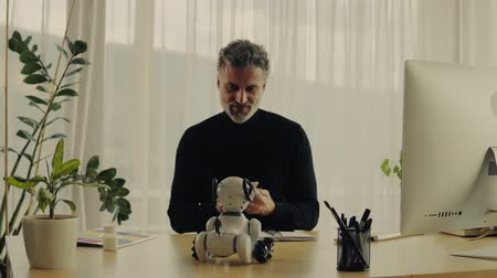 hang : Mature man with robot smart dog in home office. Stock mozgókép